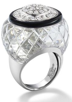 A rock crystal and diamond ring, by David Webb. The large carved rock crystal of lattice design set to the centre with a pavé-set diamond dome within a brilliant-cut diamond cluster and onyx border,ring size O, signed 'Webb'. Via Phillips.