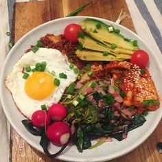 Kimchi fried red rice with blached beet leaves and sorrel, avocado, radishes, more fresh kimchi on top and a fried egg