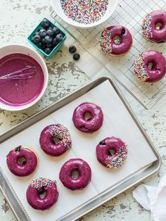 Blueberry Lemon Glazed Baked Donuts are a sweet way to start the day happy! This recipe is full of fresh blueberries - from the blueberries in the baked buttermilk donut, to the gorgeous glaze on top!