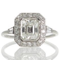 A platinum cluster engagement ring featuring a central 0.98ct emerald cut diamond bezel set with a millegrain edge within a spaced cluster of smaller round diamonds. #RutherfordJewellery #Melbourne