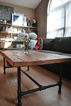 une table basse industrielle en fer, fleurs blancs, fenetre grande, murs beiges