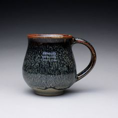 ceramic mug, handmade mug, coffee cup with black tenmoku, green celadon and wood ash glazes. $27.00, via Etsy.