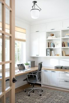 Chic first floor home office features floor to ceiling white built-in shelves, cabinets and drawers illuminated by a white frosted glass jar lantern.