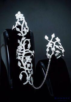 Создавая украшения, ювелиры компании не могли обойти своим вниманием великолепный стиль модерн, некогда царивший в искусстве, архитектуре, проникнувший в повседневную жизнь и покоривший сердца многих людей. И именно в стиле модерн мастера BUANJE создали это великолепное и шикарное кольцо на 2 пальца, одна из частей которых причудливыми цветами и лепестками закрывает 2 фаланги изящного женского пальчика. . Белое золото и бриллианты, сплетенные в изящный узор, подчеркнут изящество женских рук…