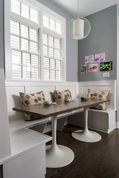 """Inspired by over-the-top transitional wainscoting throughout the house, this banquette takes on a more streamlined, transitional approach. """"This house started as a contractor build house, and this was the space that was allocated for the dining table,"""" says designer Stacey Cohen. """"We wanted to maximize it and make it family-friendly, and the only way to do that was with a custom table. The clients loved the table top, and the tulip bases came from tables we found at Ikea. The top is stained…"""