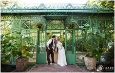 A bohemian bride wearing a flower crown and her groom pose for pictures after their wedding ceremony inside the green Woodland Mosaic Solarium at Denver Botanic Gardens.