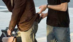Mann med lommebok i baklomma, en annen mann forsøker å stjele lommeboken