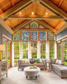 This stunning great room features a cathedral-like vaulted wood ceiling and picturesque views of the outdoors. Neutral furnishings and gray walls fade to the background and let the natural surroundings shine.