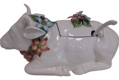 An Italian soup tureen in the shape of a recumbent bull. A la Ferdinand, this bull has muti-colored flowers decorating his neck and flowers form the handle for the tureen's lid.