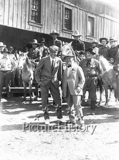 UNIVERSAL STUDIOS - 1918 - Studio head Carl Laemmle poses with a guest during shooting of a Harry Carey film on the Universal backlot.