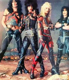 Motely Crue was a little more in the 1970s vein during their glam years, but people still forget how much more feminine their early years were. L to R: Nikki Sixx (bass), Tommy Lee (drums), Vince Neil (lead vocals), Mick Mars (lead guitar).