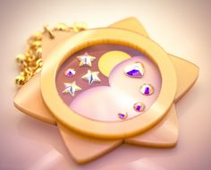 Inspired+by+Mamoru's+moon+phase+watch+in+the+manga+and+new+anime!    This+pendant+is+crafted+from+gold+pearlescent+acrylic.++The+design+on+the+center+of+the+pendant+is+printed+onto+frosted+acrylic+and+accented+with+heart+and+star+shaped+swarovski+crystals+for+that+magical+touch!    Pendant+measur...