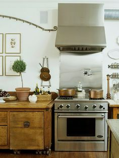 This has long been one of my favorite kitchens. Repurposed elements give this kitchen an elegant, old-world aesthetic. Beautiful framed art, topiary & copper pot accents