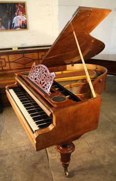 An 1870, A Bosendorfer grand piano with a walnut case and inlaid with satinwood stringing at Besbrode Pianos.
