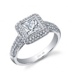 Style #SY917  1 Carat Diamond Engagement Ring    This stunning 18K white gold engagement ring features a 1 carat Princess Cut center diamond. Accentuated by surrounding diamonds and diamonds continuing down the sides of the ring totaling 0.73 carats.