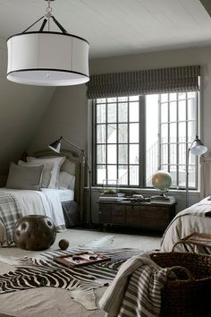 Chic shared boys' bedroom features a white drum pendant with black trim hung by leather straps illuminating two French fabric and wood headboards on twin beds dressed in white and gray linen bedding flanking a vintage trunk tucked under casement windows.
