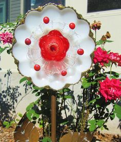 WHAT IS A PLATE FLOWER?  They are garden art creations, made of vintage glass items. I love to repurposed lovely vintage glass, because there is still beauty in them to be enjoyed. I have used them to to create something new, a one of a kind work of art! The pieces are gathered at thrift stores, flea markets, yard sales, etc. These ornaments are designed to be displayed on a stake in your garden among your plants and flowers. This particular piece is made from a mid century deviled egg…