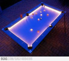 Outdoor Pool Table Features Built-In Lighting For Nighttime Play. I'm wondering if we could revamp an old pool table & just buy a set of the glowing balls from a billiards company. Outdoor Pool Table, Outdoor Fun, Outdoor Spaces, Outdoor Living, Outdoor Parties, Pool Table Lighting, Billard Design, Custom Pool Tables, Cooler Stil