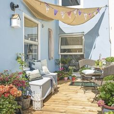 The walls in this garden terrace have been painted in a calm shade of blue to match its seaside setting. A sailboat canopy, cosy bench and bistro table and chair set make it a relaxing place to sit and watch the world go by