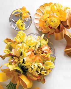 These flowers complement tables in bursts of yellow blooms, shimmery accents, and an aura of luxe glamour. Boutonnieres glitter when wrapped in shiny ribbon and accented with silver millinery leaves. A compact bouquet of ranunculus, parrot tulips, and mini cattleya orchids are held together by a rich copper bow. Lady's slipper orchids and calla lilies peek through the frilly gloriosa lilies for this maid-of-honor bouquet (bottom).