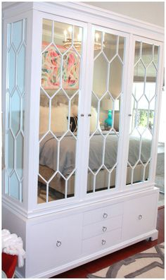 Wonderful mirrored armoire (& love those big, white fluffy pillows!)