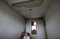 Gao Xiuzhen, 81, stands inside her damaged house in an area where land is sinking next to a coal mine, in Shiyanzhuang village of Datong. Photograph: Jason Lee/Reuters