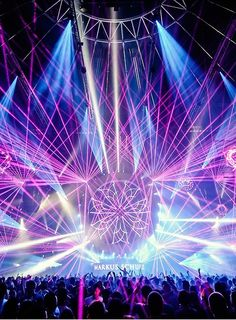 This is a photo of another EDM concert but I like that this one has a center piece of lights as well as lights from all directions. There is a lot to look at in this picture but it drew me in because of the illuminated flower in the middle, which really helps bring it all together. I also like the blue and pink lights together, the bright colors make it seem happy and exciting.