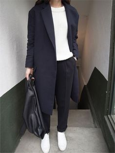 Navy blue coat, chunky ribbed white jumper, black tapered leg trousers, black leather triangular backpack + white canvas shoes