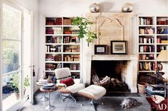 In the library of designer Isabel López-Quesada's home in Madrid, an Eames lounge chair and ottoman sit next to a French chimneypiece; the side tables are vintage. The family dog, Pepe, naps on a floor paved in Noir Belge marble. Architectural Digest, Eames Furniture, Furniture Design, Magazine Deco, Cosy Home, Bookcase Styling, Home Libraries, Piece A Vivre, Decorating Small Spaces