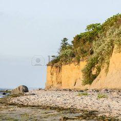 Küstenerosion an der Ostsee Strand; Küstenlandschaft mit überwucherten Felsen; Sandstrand mit Felsen und Algen Lizenzfreie Bilder