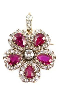 19th century pear shaped ruby and diamond cluster flower pendant-brooch, English c.1890, w/ detachable gold bangle fitting and hair pin, with 5 cluster petals each w/ a pear shaped ruby in a heart shaped diamond border, a larger round brilliant cut diamond to centre, open set in silver and gold, on a 3 stone diamond set suspension loop, the loop and the brooch fitting both detachable, together with a hinged gold bangle fitting and a metal hair pin with tremblant action.