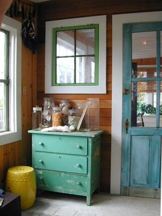 A distressed, teal door rounds out this room's rustic look while adding a touch of color  Vecchione entryway distressed furniture