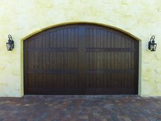 A double-size single-look version of a custom arched Model 203 garage door. Knotty Alder with a Clear Cypress overlay. Painted by hand using the Fatezzi Developed Stain System in a custom-tinted Dark Walnut finish. #fatezzi #homebeautification #fauxwood #garagedoors #gofaux