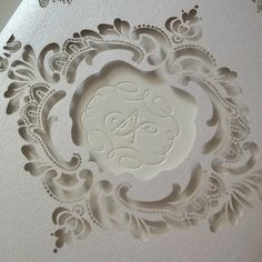 Monogram crest for a luxury wedding invitation featuring a laser cut lace sleeve