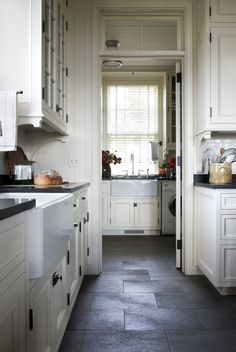 Loving the elements of this kitchen.from the slate floor, to the white cabinetry (w/ glass-fronts), to butler's pantry and black granite counters :) Reminds me of my folks' new kitchen. Slate Floor Kitchen, Kitchen Tiles, New Kitchen, Kitchen Dining, Kitchen Cabinets, White Cabinets, Black Slate Floor, Kitchen White, Country Kitchen Flooring