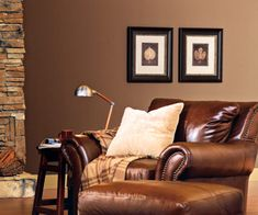The milk chocolate wall color in this warm living room feels warm and earthy. Traditional leather, cozy fabrics, and a stone fireplace keep with the theme. A pair of botanical prints stand out with pale mats.    Dutch Boy; Firewood B14-1; dutchboy.com