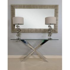 Cleo console table in polished stainless steel with glass top.
