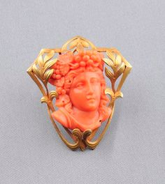 14kt Gold and Coral Cameo Pendant/Brooch, depicting a classical maiden with grapevine diadem, in a scrolling foliate frame, lg. 1 3/4 in. Art Nouveau or Art Nouveau style. [Maybe. Closest I could come]