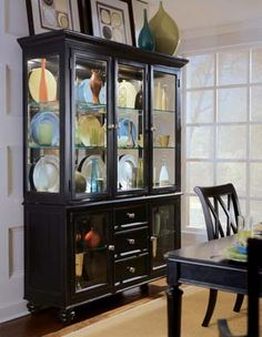 Like the propped up paintings and vase on top of china cabinet