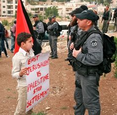 """""""East Jerusalem is Palestine. Stop Settlement.""""  A Palestinian boy faces an Israeli riot control police officer at a Sheikh Jarrah demonstration  [follow this link to find a short video and analysis contemplating the effect of war on children: http://www.thesociologicalcinema.com/videos/creating-empathy-the-effect-of-war-on-children]  Photo credit: Lisa Goldman"""
