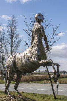 #Ingwershörn #Witzwort Wie ein Wächter steht der stählerne Zentaur an der Bundesstraße. Im unteren Bereich hat die Figur den Körper eines mächtigen, sich aufbäumenden Pferdes. Im oberen Bereich sitzt der muskulöse Körper...