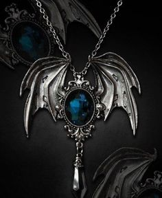 £20    Midnight Bat Wing Necklace     Pendant is made of durable metal in antique silver colour (pewter).  It presents a Turquoise Stone Encased In Bat Wings     On the back of pendant is a safety pin, so you can wear it also as a brooch.  Pendant is on a long chain.    Measurements:  Width: 3 cm  Length: 5,5 cm  Chain length: 80 cm