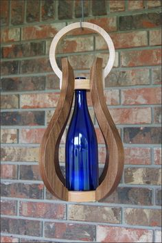 This is a beautiful decorative handcrafted wooden frame wine bottle candle lantern with a repurposed 750 ml wine bottle. It is beautiful whether or not the candle is lit and is a unique addition to your home decor.  You can hang or carry this candle lantern and use it as a decorative table display. This can be used in any interior room or outside in a covered porch, deck or lanai area.   Lift the wine bottle to light the candle. Then when you are ready to extinguish the candle...