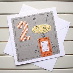 This cute, one-off, handmade 2nd birthday card has been designed and made by myself using the technique of free motion machine embroidery. It is lovingly made to create a really special birthday card for a little one to celebrate their big day. Individual pieces of fabric have been cut out by hand and then machine stitched into position to create the robot and the number. The word today has been stamped by hand onto the fabric. The card is an original fabric design and is not a photographic…