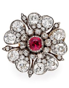 A Victorian Ruby and Diamond Tudor Rose Ring, England, circa 1860. Designed as a Tudor Rose, with a central cushion-shaped ruby and pavé-set diamond petals, later ring attachment mounted in silver and gold. #Victorian #TudorRose #ring