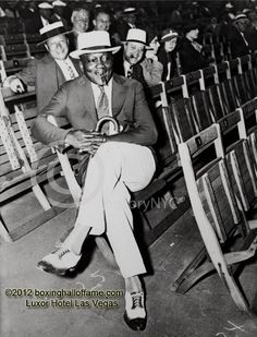 For all you youngsters who are accustomed to seeing the casual attire worn by the crowd at current day boxing events - as late as the early 60's EVERYONE wore jackets, ties and HATS! Here's a shot of a good looking guy at the Baer - Carnera fight of 1934 held at the Madison Square Garden Bowl in Long Island City New York. Do you recognize him? One of the legendary greats of all time. And how about those cool shoes!  boxinghalloffame.com