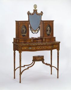 Dressing table 1820-1835:In Britain painted satinwood furniture based on styles of the 1780s and 1790s remained popular until at least the 1830s. Cabinet makers adapted and changed the designs slightly to satisfy the fashions of the time. This dressing-table was possibly adapted from a design published in 1788 for a combined writing- and dressing- table. It may have been made in the 1830s as there are hand made screws used in the construction and handles made of Sheffield plate.