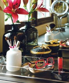 Beautifully organised vanity. I especially love the gorgeous stout bottle with a single lily