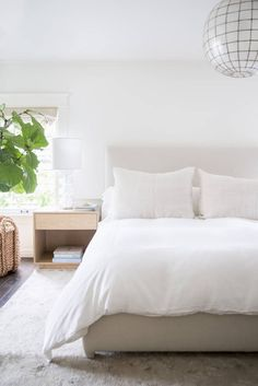 In the master bedroom, a capiz-shell fixture provides a glamorous counterpoint to crisp white bed linens from Restoration Hardware.