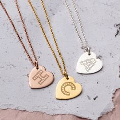 """A treat for yourself or the perfect gift for your best friend, this Personalised Letter-In-Lights heart Necklace is a favourite with a brilliantly engraved initial on the front. The typeface reminds us of old movies and fairgrounds. Its the subtle way to wear your sparkle!  Make it that extra bit special by personalising the reverse with words, message, names and dates of your choice.  Choose from 3 metal types either silver, 9ct rose or yellow gold plated, the pendant includes an 18"""" ch..."""